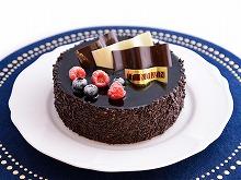 チョコレートでコーティングされた上にベリーとチョコの飾りが飾られている